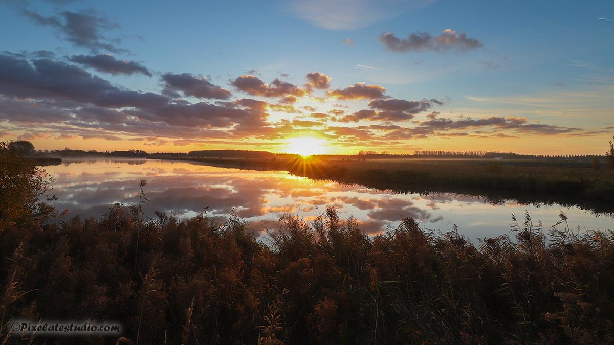 Foto van een mooie zonsopkomst foto genomen aan een kreek in Zeeland