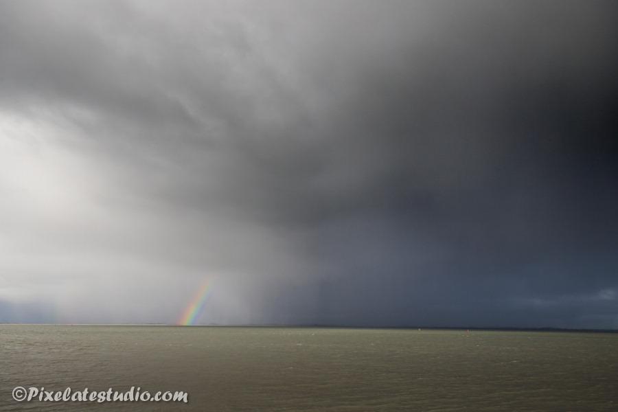 foto van een dreigende lucht met regenboog