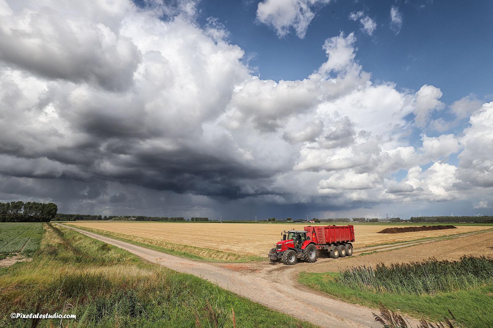 3d landschapsfoto, tractor rijd mest het afgereden graanveld op.