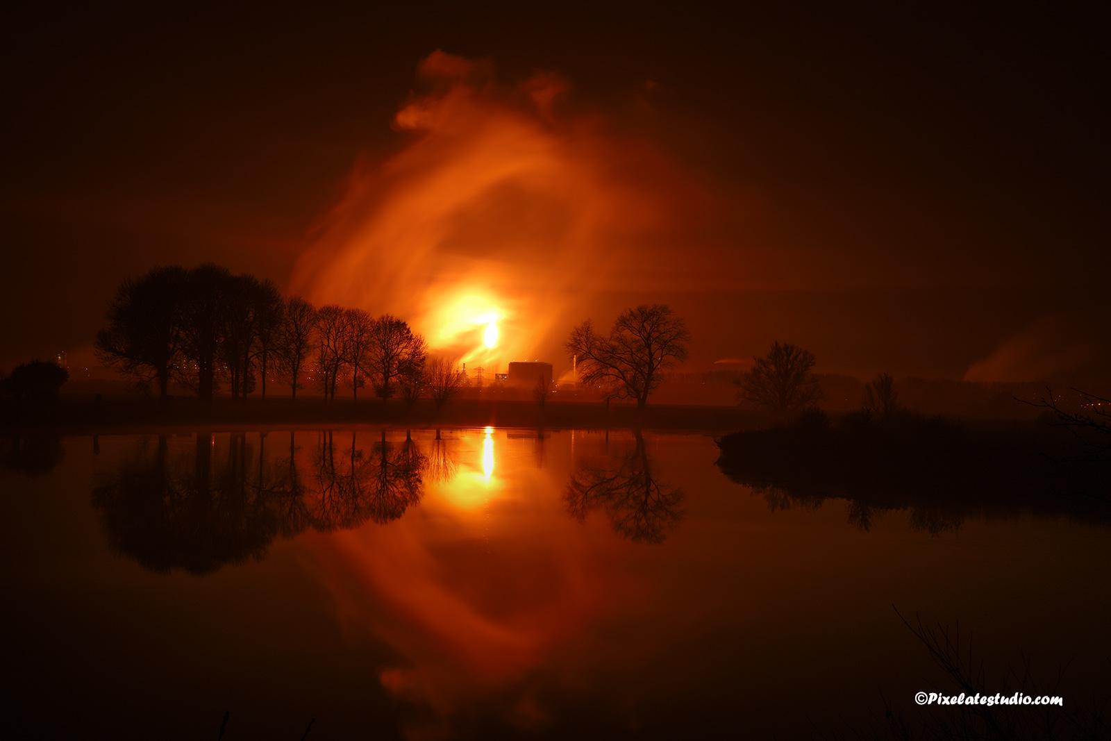 aparte landschapsfoto s'nachts genomen met bomen die spiegelen in het water