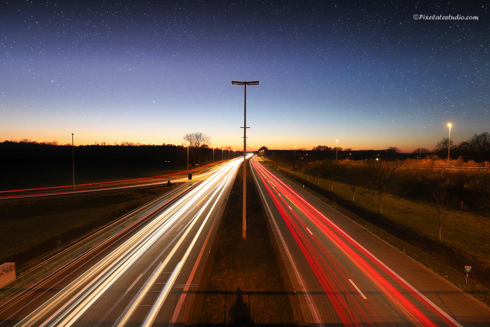foto met lange sluitertijden genomen op een viaduct boven een autobaan , zodat je de verlichting van de auto's als lichtstrepen ziet