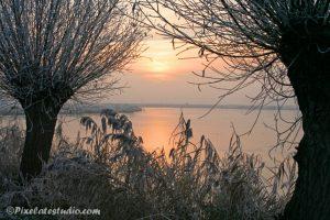 Zonsondergang op de kreek met bevroren ijs