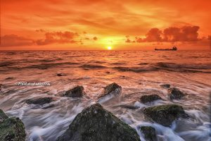 Strand foto van een mooie zonsondergang aan zee met een schip dat voorbij vaart,
