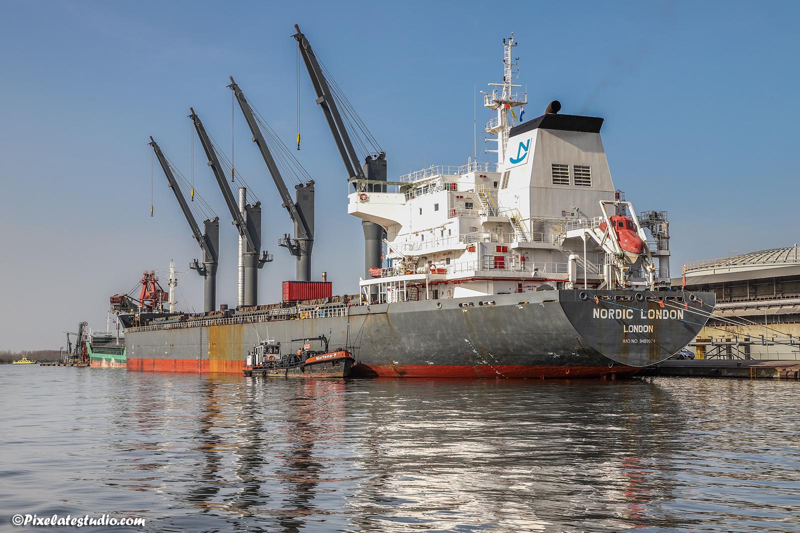 mooie foto van vrachtschip met spiegeling dat in de haven word bevoorraad door een bunkerbootje