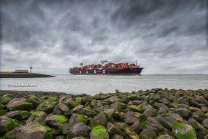 foto van enorm containerschip , vaart langs pier in Terneuzen