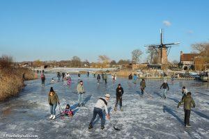 Foto van het schaatsen bij de molen , ijspret