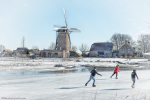 ijspret bij de molen een oud Hollands plaatje van de ijspret in de winter met schaatsen op natuurijs.