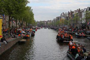 foto van feestende mensen op de bootjes op de prinsengracht Amsterdam