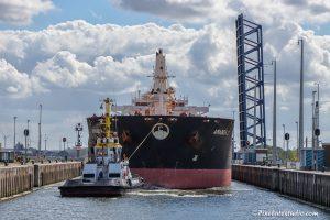 Sleepboot met groot vrachtschip vaart defoto van sluizen van Terneuzen binnen