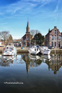 mooie foto van de jachthaven in Sas van Gent, met de herenhuizen en de kerk mooi in beeld