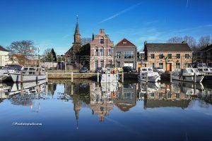 mooie foto van de jachthaven in Sas van Gent, met de herenhuizen mooi in beeld, ook de kerk spiegelt mooi in het water van de jachthaven